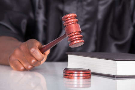 striking: Close-up Of Male Judge Hand Striking The Gavel In A Courtroom