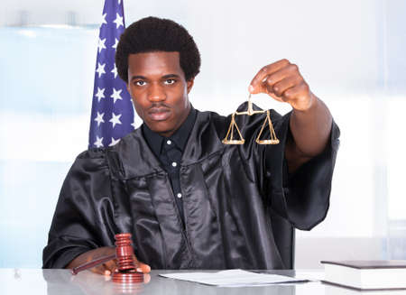Portrait Of A African Judge Holding Gavel And Scale In Courtroom photo