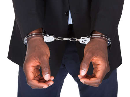 jail background: African Man With Handcuffed Hands Isolated On White Background Stock Photo