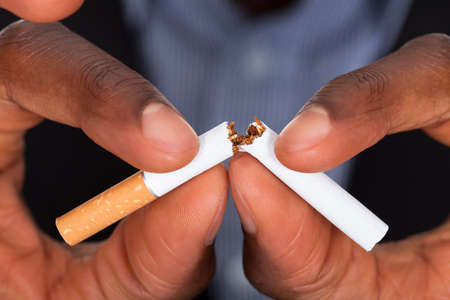 no problems: Close-up Of Human Hands Breaking The Cigarette