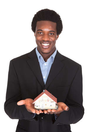 Young African Businessman Holding House Model Isolated Over White Background photo