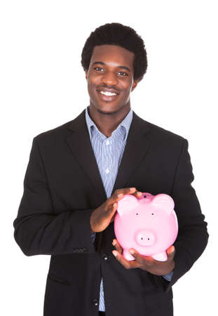 american money: Portrait Of Young African Businessman Holding Piggybank Over White Background