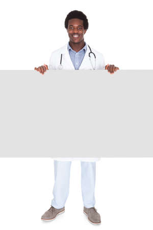 Portrait Of A Happy African Male Doctor Standing Behind Placard On White Background photo