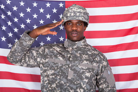 saluting: Portrait Of Afro-american Army Soldier Saluting In Front Of American Flag