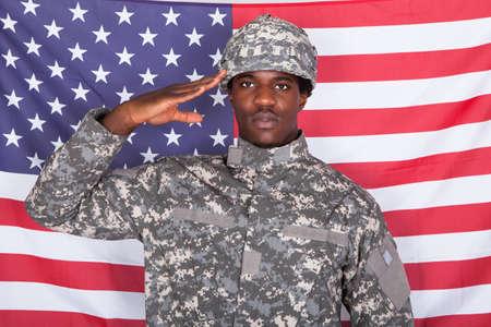 estrellas  de militares: Retrato de Soldado afroamericano que saluda delante de la bandera americana Foto de archivo