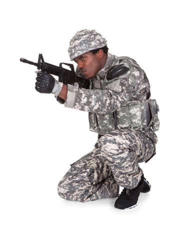 Portrait Of A Male African Soldier Aiming With Gun Isolated Over White Background photo