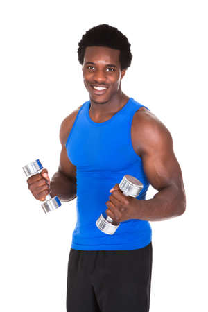 men exercising: Portrait Of Happy African Man Exercising With Dumbbells Over White Background