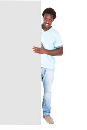 Happy Young African Man In Casual Standing Behind The Placard Over White Background photo