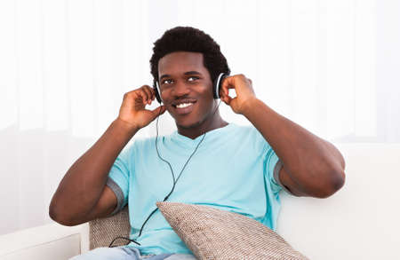 Happy Relaxed Young African Man Sitting On Couch Listening Music On Headphone Stock Photo - 21479001