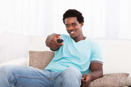 lcd tv: Happy African Young Man Watching Television At Home