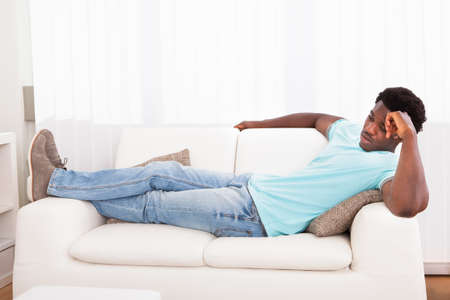 tired man: Lazy Worried African Young Man Sitting On Couch At Home
