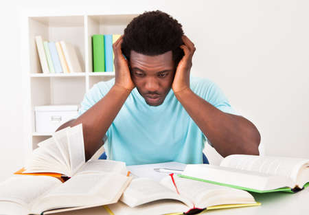bored: Worried Young African Man Studying At Home With A Lot Of Books