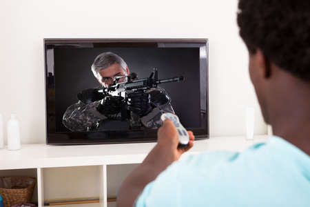 lcd tv: Happy African Young Man Watching Army Solider With Gun In Television At Home