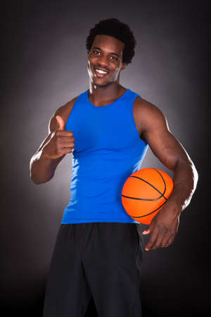 Young African Man Holding Basketball Over Black Background photo