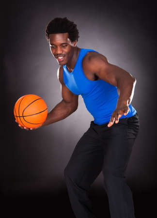 Young African Man Carrying Basketball Over Black Background photo