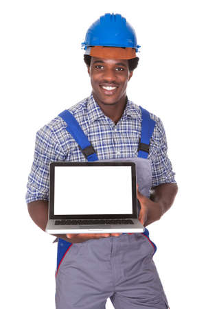 Happy Craftsman Holding Laptop Over White Background photo