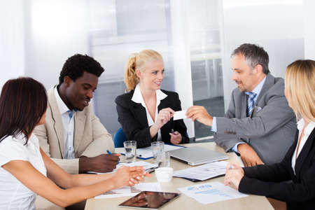 corporation: Businesspeople In A Meeting Exchanging Visiting Card Stock Photo