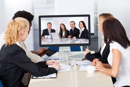 Group of male and female businesspeople at video conference photo