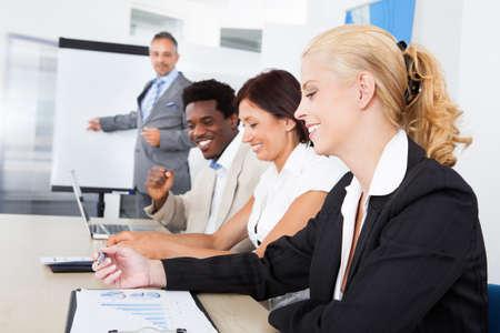 curso de capacitacion: Grupo de ejecutivos de negocios tomando notas durante una reuni?n en la oficina Foto de archivo