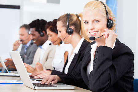 telephone headsets: Happy Co-workers Wearing Headsets Working In Call Center