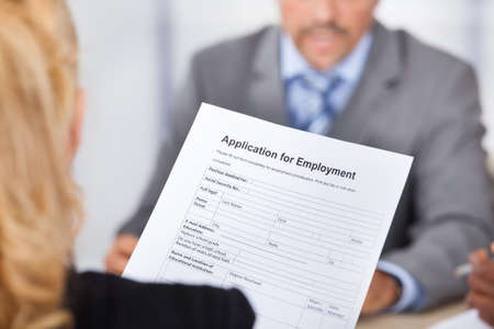 Businesswoman Sitting In Front Of Businessman Holding Application Form 免版税图像