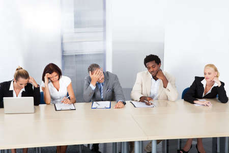 bored man: Group Of Tired Corporate Personnel Officers In A Row