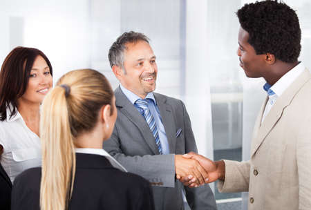 acceptance: Two Businessmen Shaking Hand In Front Of Colleagues Stock Photo