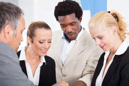 socializando: Grupo de empresarios felices multirraciales Discutir Juntos En La Oficina