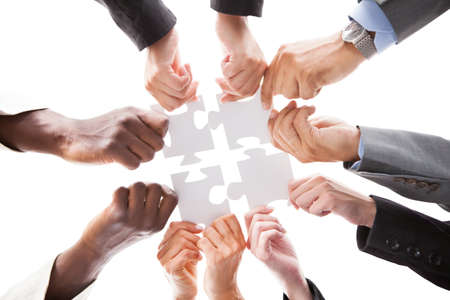 group cooperation: Close-up Photo Of Businesspeople Holding Jigsaw Puzzle