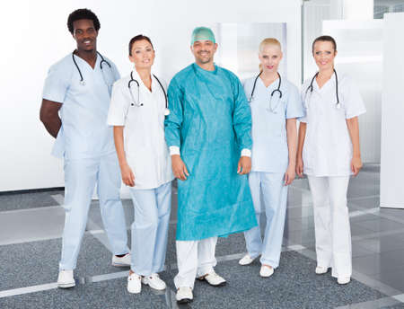 Happy Mature Doctor In Surgical Gown With His Coworkers photo