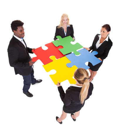 Multiracial Businesspeople Holding Jigsaw Puzzle Over White Background photo