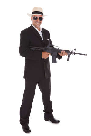 kill: Happy Mature Business Man Holding Gun Over White Background