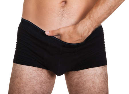 Close-up of man putting his hand inside underwear photo