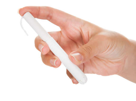 gynecologic: Close-up of hand holding tampon over white background Stock Photo