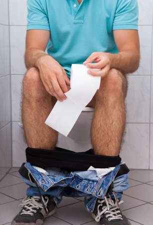 Close-up of a man in toilet holding tissue photo