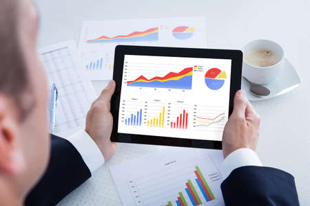 Businessman Analyzing Graph On Digital Tablet In Office photo
