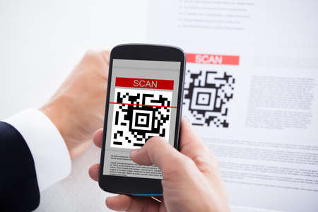 Close-up Of Businessman Scanning A Barcode Using Cell Phone photo