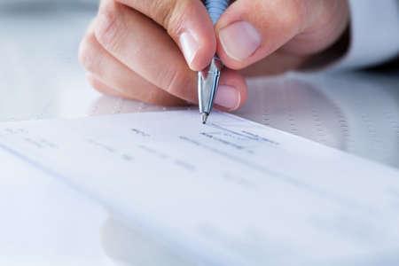 Een Mannelijke Hand invullen van het bedrag op een cheque