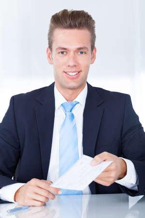 dinero falso: Retrato de joven feliz de negocios que ofrece Cheque