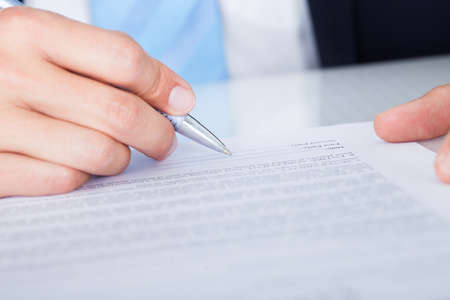 signing authority: Close-up Of Businessman Signing Contract Paper With Pen Stock Photo
