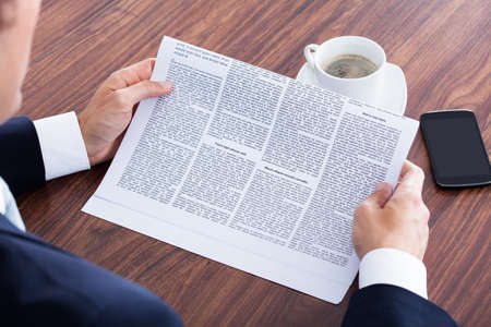 reading news: Close-up Of Businessman Reading News On Newspaper