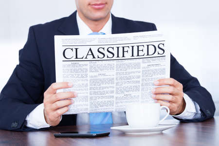 job hunt: Close-up Of Young Businessman Reading Classifieds On Newspaper Stock Photo