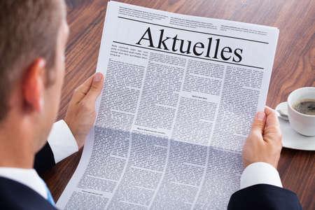 見出しの現在のニュースと新聞を読むビジネスマン