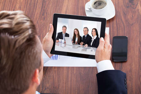 conferencing: Imprenditore Video Conferencing su tavoletta digitale In Ufficio