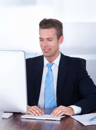 Portrait Of Happy Young Businessman Using Computer In Office Stock Photo - 21668688
