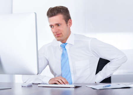 working stiff: Businessman Using Computer Suffering From Back Ache Stock Photo