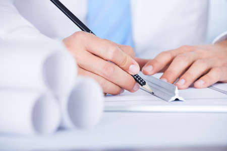 Close-up Of Male Architect Working On Blueprint At Desk Stock Photo - 21668720