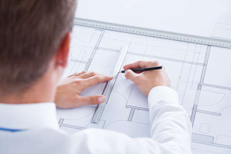draftsman: Close-up Of Male Architect Working On Blueprint At Desk