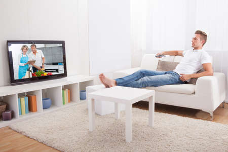 high definition television: Young Man Sitting On Couch And Watching Movie At Home Stock Photo