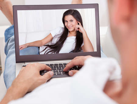 hombros: Hombre joven con un Videochat con la mujer en la computadora port�til